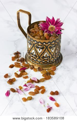 Raisins in beautiful vintage cup on a white ceramic table