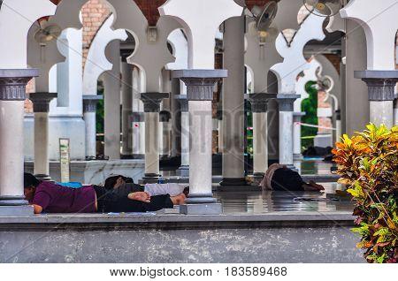 KUALA LUMPUR, MALAYSIA - OCTOBER 26, 2012: People having rest in the mosque in the cosmopolitan city of Kuala Lumpur Malaysia