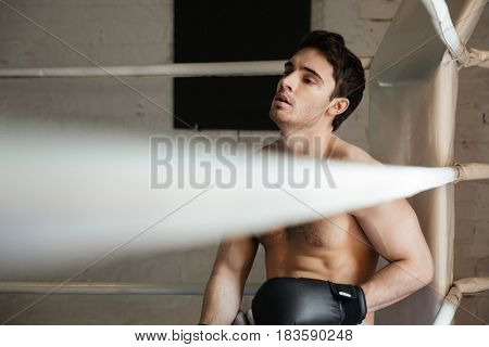 Tired young man boxer relaxing in the corner of the gym