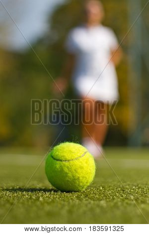 Tennis ball on tennis court with a blurred player