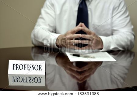 Professor at desk with papers and card making hand gestures