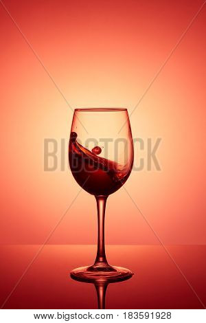 Glass of wine. Red Wine Abstract Splashing. Wine splashing in glass acrylic background studio lighting