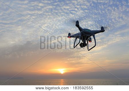 KAGAWA, JAPAN - APRIL 22, 2017: Remote controlled drone Dji Phantom4Pro equipped with high resolution video camera flying above the sea against a sunset sky.
