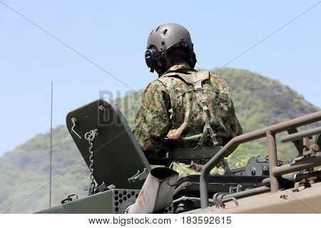 KAGAWA, JAPAN - APRIL 23 2017: Japanese soldier in the armored vehicle going to the Zentuji military base