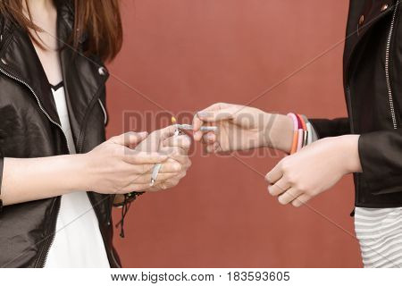 Young women smoking weed outdoors on color background