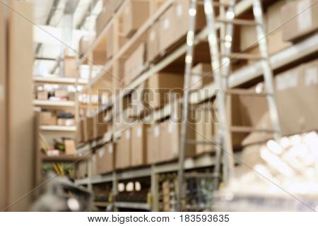 Boxes with goods in wholesale warehouse, blurred view