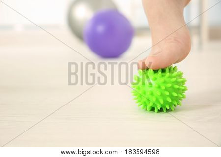 Foot of woman doing exercises with rubber ball in clinic