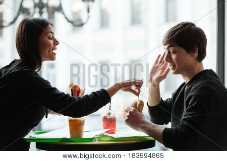 Young cute woman trying to eat burger of her brother while they sitting near window in cafe