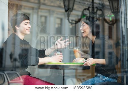 Image of smiling young man sitting in cafe with his sister drinking juice. Looking aside.
