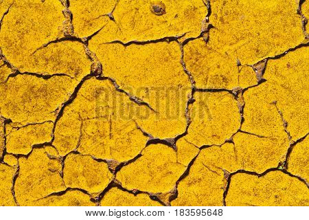 Bright and dirty yellow surface with rives and fractures.