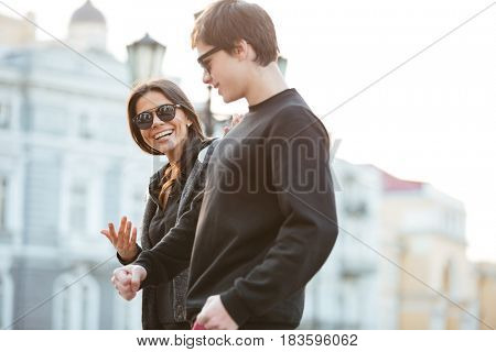 Image of smiling young woman walking outdoors with her brother. Looking aside.