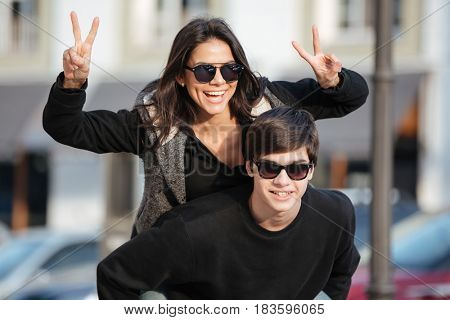 Picture of young cheerful woman walking and have fun outdoors with her brother. Looking at camera showing peace gesture.