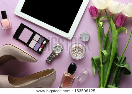 Beautiful composition of cosmetics and accessories with tulips on table