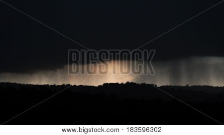 April snow falling over Bath, Somerset, UK. Dark clouds bring sleet and snow at dusk seen over countryside to the east of the UNESCO World Heritage City