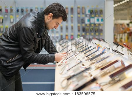 young male customer choosing smartphone in the mobile phone shop