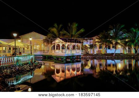Cayo Coco island, memories Caribe hotel, Cuba, June 26, 2016, gorgeous amazing, inviting view of Memories Caribe hotel grounds lighted with various warm lights, reflected in water at evening time in tropical garden