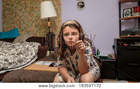 nice amazing closeup view of serious unhappy little girl sitting alone in her room