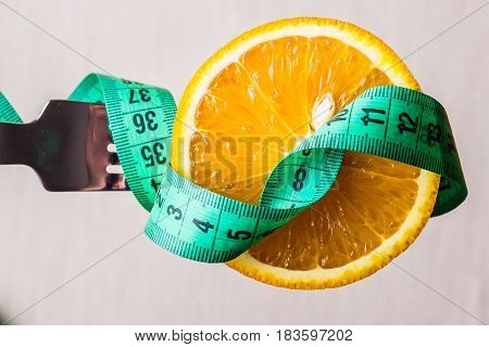 Diet healthy eating and slim body concept. Closeup green measuring tape centimeter and orange fruit