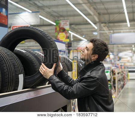 male customer choosing new tires in the car hypermarket. He is taking tire from shelf
