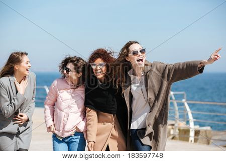 Laughing carefree female friends walking near sea in good weather
