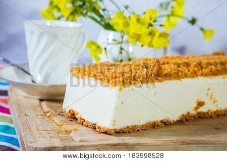 Professional bakery. The vase with daisies and porcelain cup with hot tea. White cheesecake with orange sweet crumbs