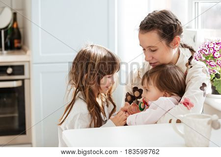 Young mother with her little daughters sitting in kitchen