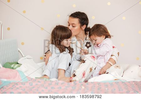 Mother kissing her daughter while other child eating at home