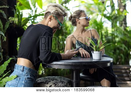 Lovely girls by the round table in the cafe with many green plants. One girl in sunglasses looks to the side, other looks at her cellphone and smiles. Daylight shines on them. Closeup. Horizontal.