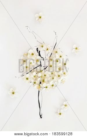 Hand drawn beautiful ballerina wearing dress made of natural flowers and posing on a tiptoe isolated over white. Fashion illustration