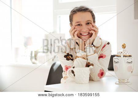 Smiling young woman wearing pajamas sitting in kitchen