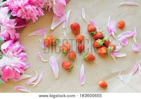 Top view of peonies and strawberries lie on a table on kraft paper photo in natural light