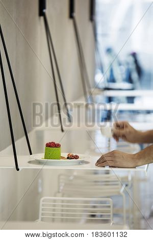Green cake with raspberries and few berries on the white plate on the small rack on the blurry background in the confectionery. There are hands with a cup next to the plate. Closeup. Vertical.
