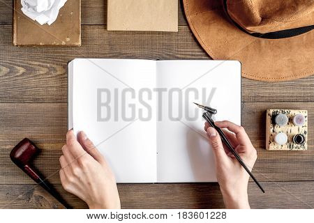 author office in professional writer concept with hands and hat on wooden work desk background top view