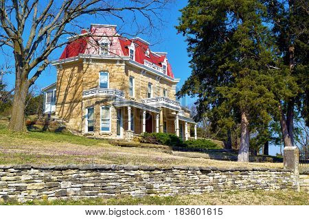 Stone historic mansion built in the 1880s with a large yard taken on the Kansas Plains