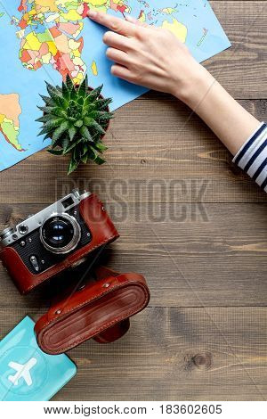 tourist stuff with photo camera and wordwide map on wooden table background top view mockup