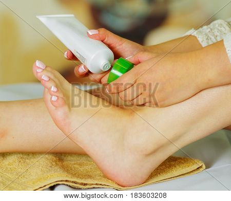Woman caring about her feet and putting hydrating cream on it with cream bottle.