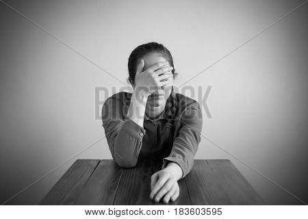 Depressed woman sitting at a table covering her face with her right hand. Manipulated black and white image, vignette is added.
