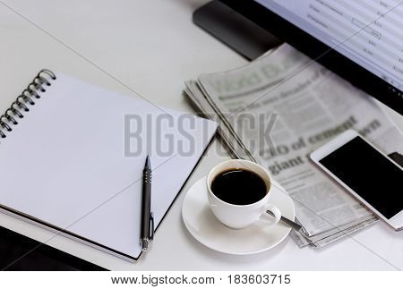 cup of coffee with newspapercomputer and smartphone on white table.