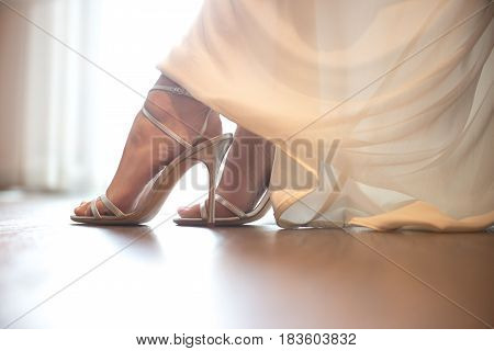 Bride wearing wedding shoes. Close-up details of brides feet wearing shoes.