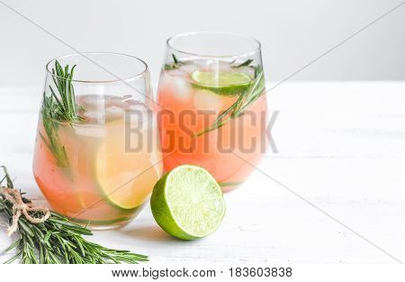 fitness cocktail in glass with cut lime and fresh rosemary on white table background mock-up