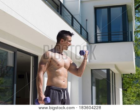 young handsome man doing morning exercises in front of his luxury home villa