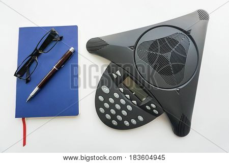 isolated voip IP conference phone with notebook and eyeglasses for taking minute of meeting in office