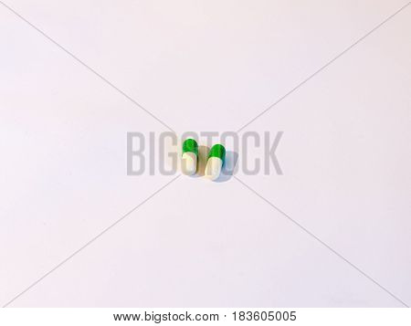 Two Basic Generic Pills On A White Background White And Green Drugs