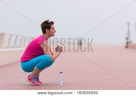 very active young beautiful woman stretching and warming up on the promenade along the ocean side to keep up her fitness levels as much as possible