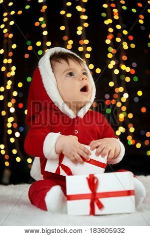 baby portrait in christmas decoration, dressed as Santa, boke lights on dark background, winter holiday concept