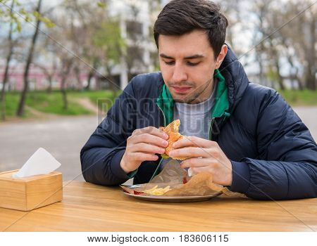 A portrait of young man eating a burger in street food cafe. Fast food eating. He is looking at the burger