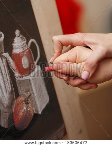 The man draws a still life with pastel crayons in an art school. The teacher helps to correct the defects in the picture. Hands close-up. Courses of drawing for adults.