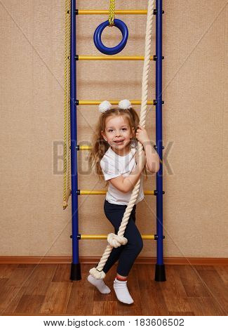 Little girl in sportswear riding on a tightrope. The concept of a healthy lifestyle from a young age. Children's sports.