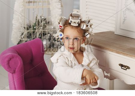 Little girl fashionista. A girl in a curler and a robe is sitting on a chair. Little coquette. Human emotions.
