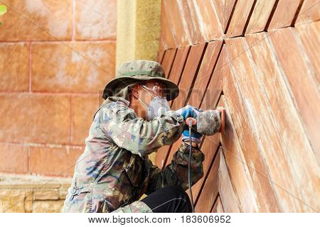 A worker use electric sander on wooden door